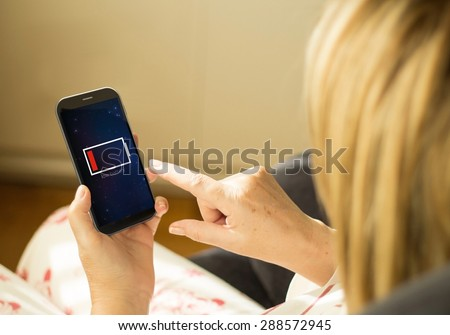 energy and modern lifestyle concept: young woman with a low battery interface on a 3d generated smartphone. All screen graphics made up. - stock photo