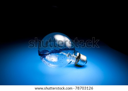 Energy concept. Light bulb with water in side on blue ground in empty room