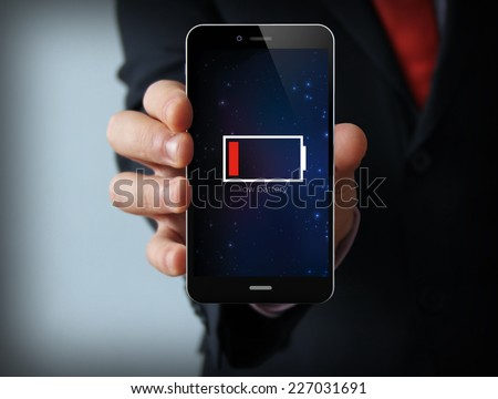 energy concept: Male hand holding a low battery mobile phone  - stock photo