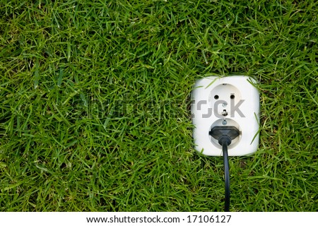 energy concept outlet in grass - stock photo