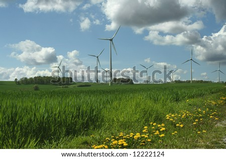 energy concept - wind turbines in beautiful summer landscape, amazing cloudscape