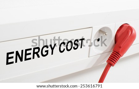 Energy cost imaged by a red plug and an electrical outlet - stock photo
