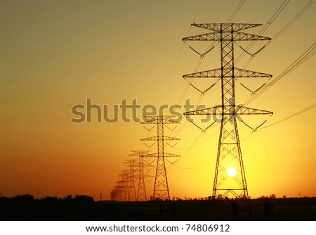 Energy Distribution Network - Electricity Pylons against Orange and Yellow Sunset - stock photo