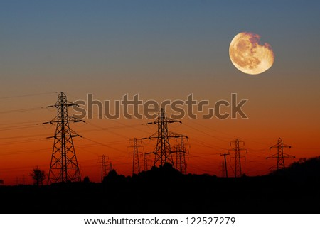 Energy Distribution Network - Electricity Pylons against Orange sky and Yellow Moon - stock photo