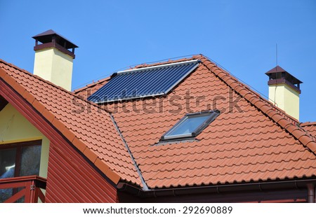Energy efficiency concept. Closeup of solar water panel heating on red tiled house roof with lightning protection and chimney. - stock photo
