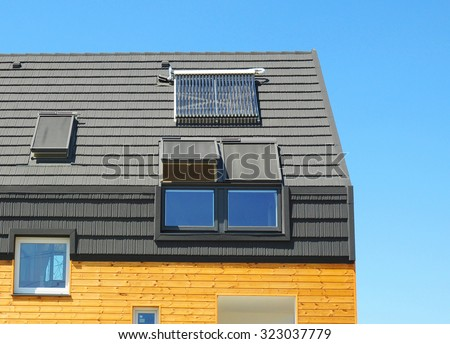 Energy Efficiency New Passive House Building Concept. Closeup of Solar Water Panel Heating, Dormers, Solar Panels, Skylights, Ventilation and Air Conditioning Systems Installed on Tiled House Roof  - stock photo