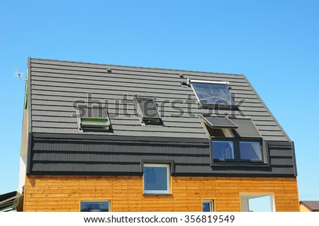 Energy Efficiency New Passive House Building Concept. Closeup of Solar Water Panel Heating, Dormers, Solar Panels, Skylights, Ventilation and Air Conditioning Systems Installed  - stock photo