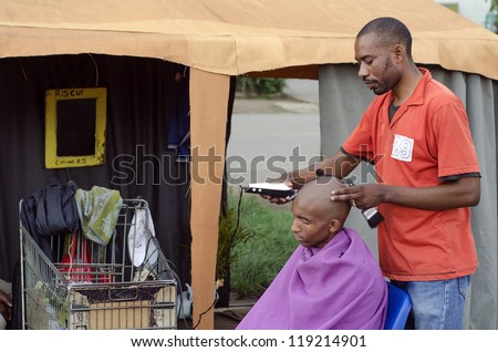 Energy efficient African small business barber with inverter and car batteries in trolley - stock photo