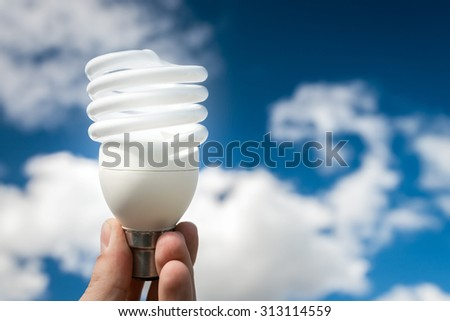 Energy efficient bulb in hand with blue sky in background - stock photo