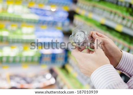 Energy efficient lighting choice: closeup on hands holding or selecting LED diode light bulb lamp in DIY department store - stock photo