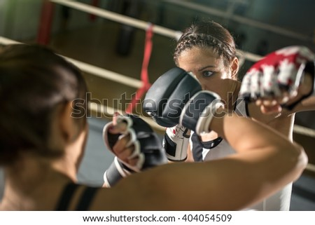 energy female boxer practicing in the boxing ring - stock photo