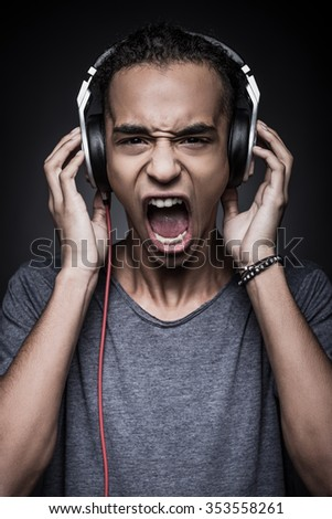 Energy inside me! Furious young African man adjusting headphones and looking at camera with mouth open while standing against black background - stock photo