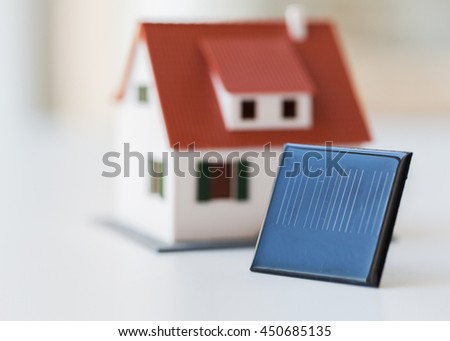 energy, power source, environment and ecology concept - close up of living house model and solar battery or cell - stock photo