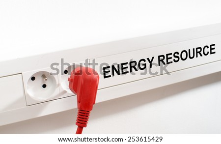 Energy resource imaged by a red plug and an electrical outlet - stock photo