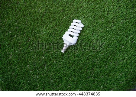 Energy saving bulb in the grass. Horizontal photo - stock photo