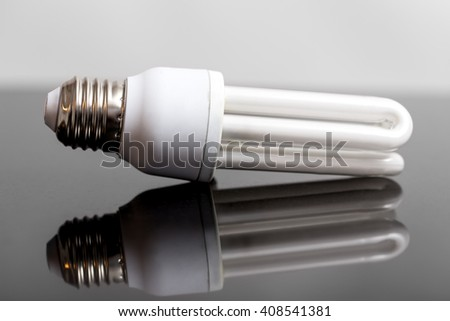 energy saving bulb on a black background with reflection - stock photo