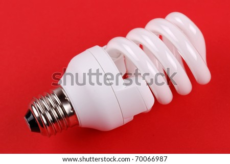 energy saving bulb on red background - stock photo