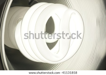 Energy saving compact fluorescent bulb glowing inside a round metal dish - stock photo