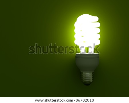 Energy saving compact fluorescent light bulb glowing on green - stock photo
