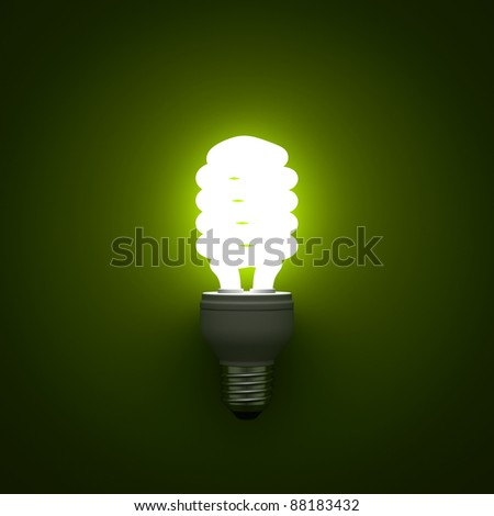Energy saving compact fluorescent light bulb glowing on green background - stock photo