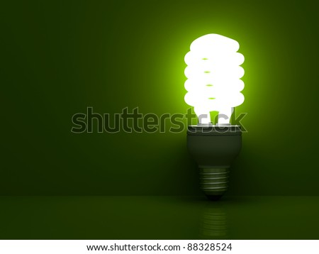 Energy saving compact fluorescent light bulb glowing on green background with reflection - stock photo