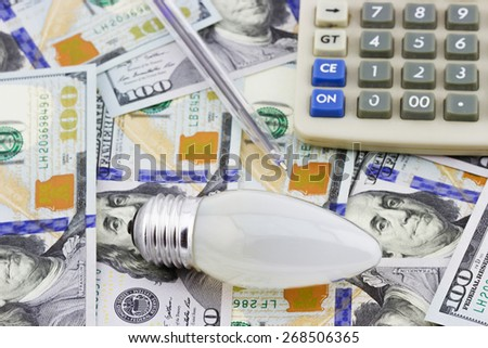 Energy saving concept. Electric light bulb with pen and calculator on dollar bills background - stock photo