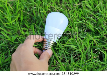 Energy saving concept. Hand holding light bulb on green grass background,. - stock photo