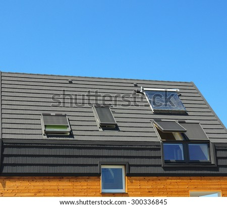 Energy saving concepts in new building energy efficiency roof design. Modern skylights, dormers, bitumen tiles,  and solar water panel heating. - stock photo