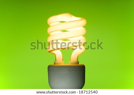 Energy saving fluorescent light bulb on green background. Space for text. - stock photo