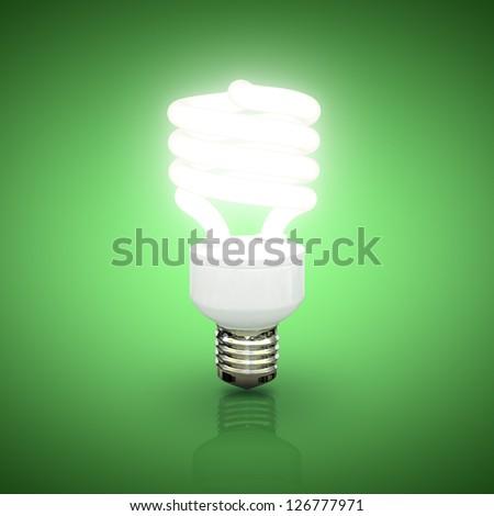 Energy saving fluorescent lightbulb on green background - stock photo