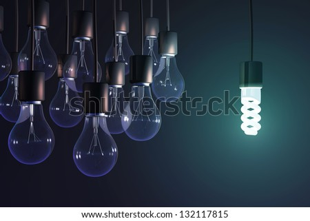 energy-saving lamp among the gray bulb - stock photo