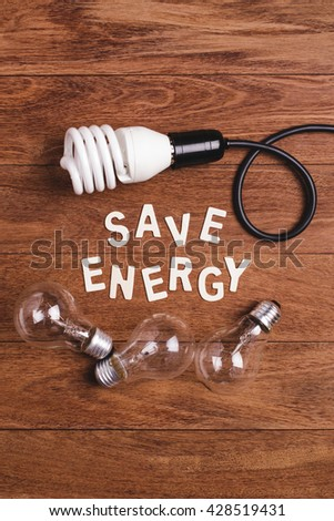 """Energy saving lamp and incandescent lamp and """"save energy"""" word on wooden background. Concept for saving energy. Concept for eco-friendly. Concept for global warming. - stock photo"""