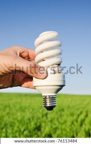 energy saving lamp in hand over green field - stock photo
