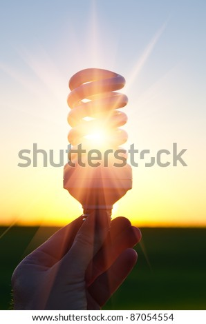 energy saving lamp in sunbeam over sunset - stock photo