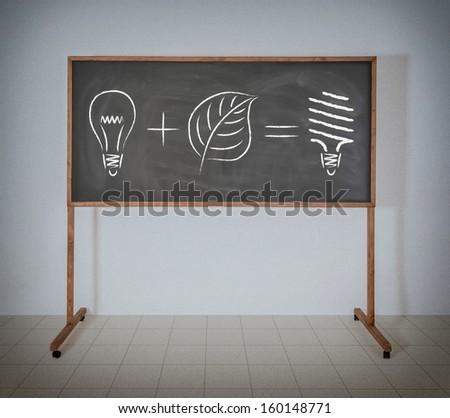 Energy saving lamp on a school blackboard - stock photo