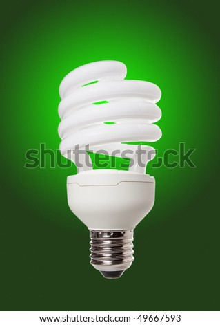 Energy saving lamp on the green background - stock photo