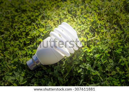 Energy saving lamp on the green grass - stock photo