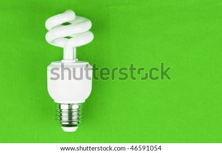 Energy saving lamp over green background.