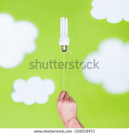 Energy saving light bulb as a balloon in the sky, ecological concept - stock photo
