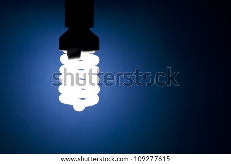 Energy saving light bulb glowing on blue background - stock photo