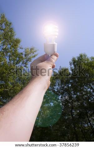 Energy saving light bulb lit outside - stock photo