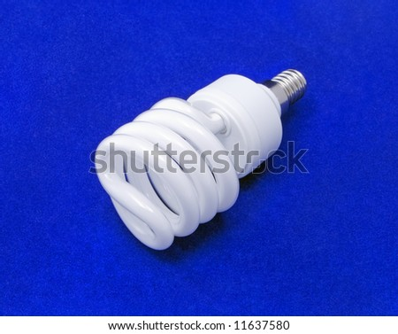Energy saving light bulb on a blue background. - stock photo