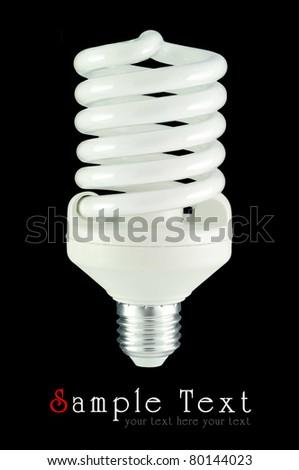 Energy saving light bulb on black background - stock photo