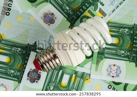 Energy saving light bulb on Euro banknotes - stock photo