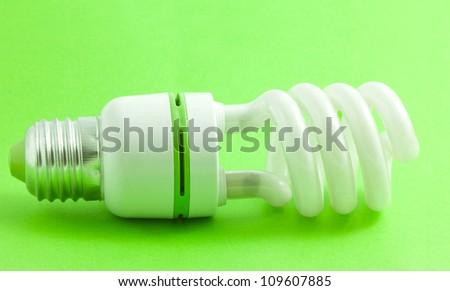 Energy saving light bulb on green - stock photo