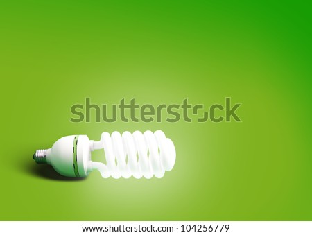energy saving light bulb on green background - stock photo