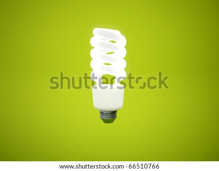 energy saving light bulb on green background - stock photo