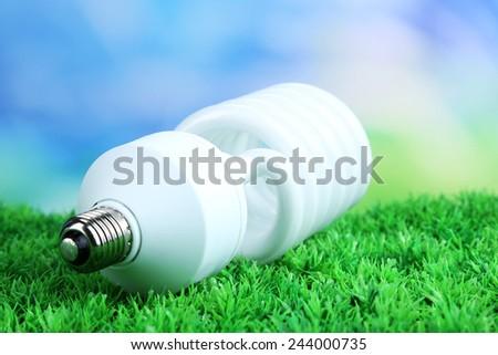 Energy saving light bulb on green grass, on bright background - stock photo