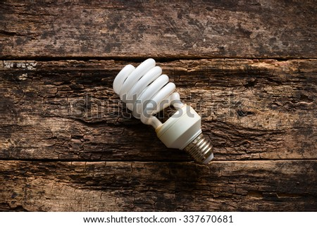 Energy saving light bulb on wooden background - stock photo