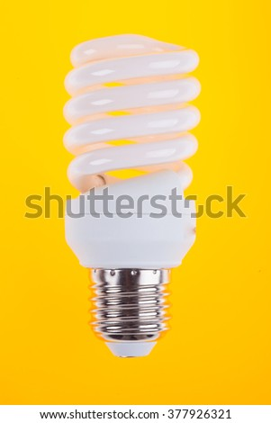 energy saving light bulb on yellow background - stock photo